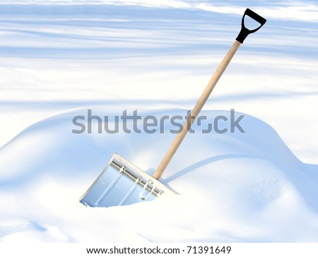 Shoveling snow from driveway: shovel in snow - stock photo