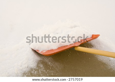 shoveling snow with a shovel after a snowfall - stock photo
