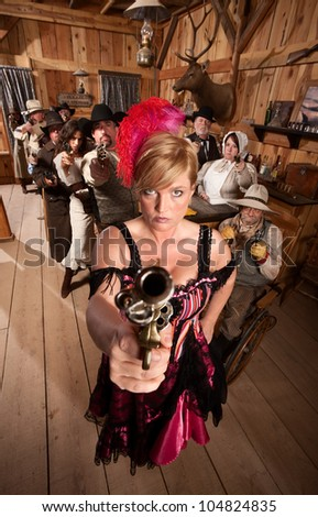 Show girl points her revolver in old west bar - stock photo