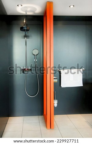 Shower all in black with orange divider  - stock photo