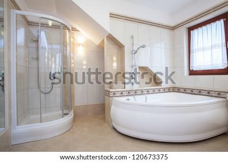 Shower and big bath in beige bathroom interior - stock photo