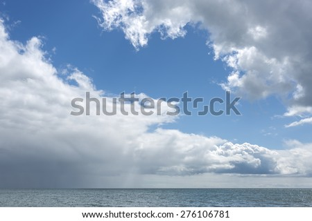 shower clouds over the sea - stock photo