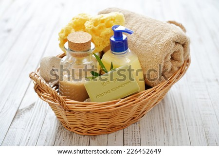 "Shower gel with  olive soap and bath towels in basket on wooden background. The words on soap translates as ""best quality""  - stock photo"