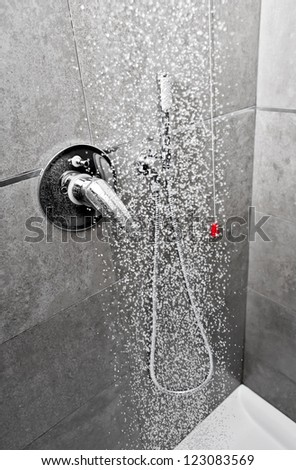 Shower handle with water falling on the floor