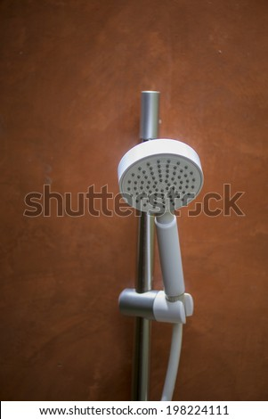 Shower head and tap on a orange background - stock photo