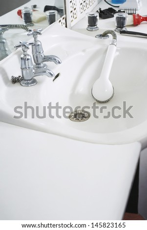 Shower head in sink at barber shop - stock photo
