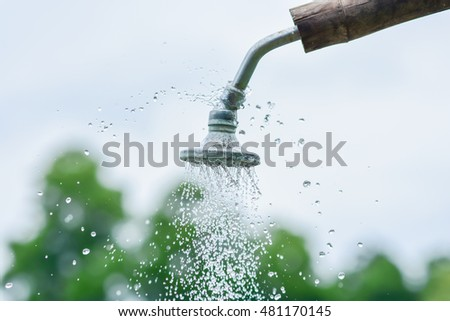 Shower head with dropping water on green and sky background.