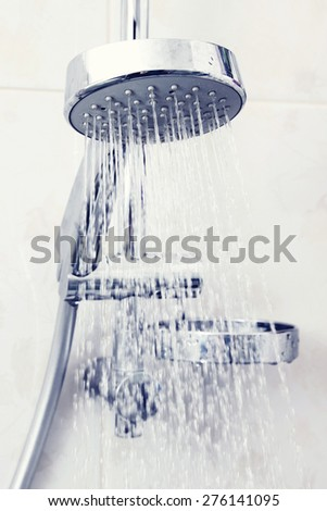 Shower head with water. Color toning applied. - stock photo