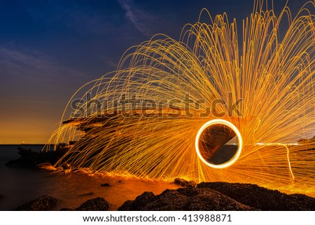 Showers of hot glowing sparks from spinning steel wool - stock photo