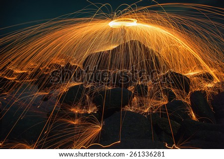 Showers of hot glowing sparks from spinning steel wool on the rock and beach - stock photo