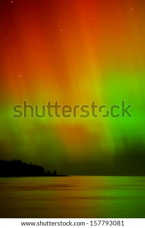 Showers of red and green beams of color from the northern lights. - stock photo
