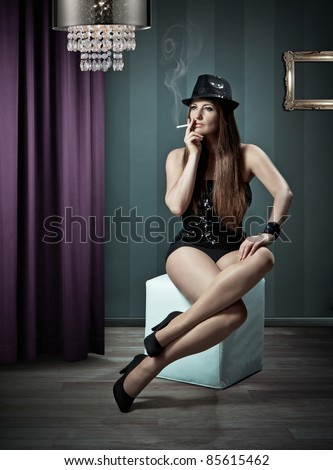 showgirl sitting on a stool and smoking - stock photo
