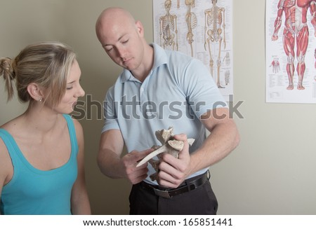 Showing female patient sample spine in his office - stock photo
