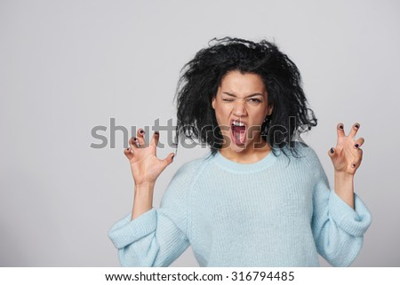 Showing her wild side. Young mixed race african american - caucasian woman posing in woolen sweater growling at you and gesturing a claw shape with her hands, over gray background