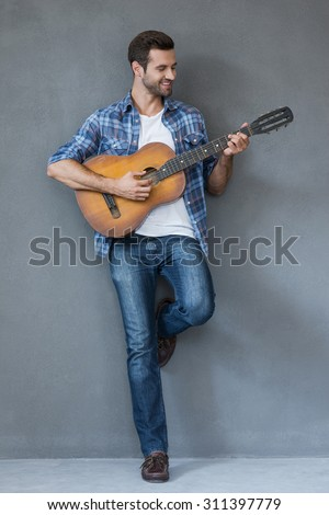 Showing his musical talent. Full length of happy young man playing the guitar and smiling while standing against grey background - stock photo