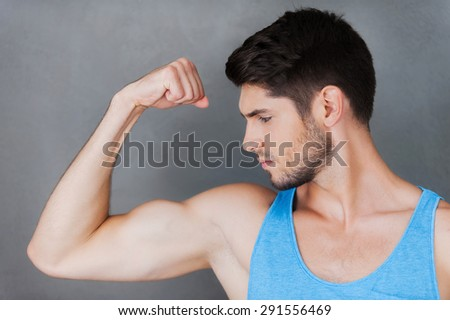 Showing his perfect bicep. Confident young muscular man posing while standing against grey background  - stock photo