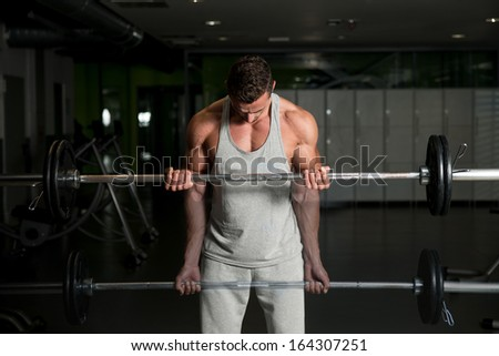 Showing How To Train Biceps. Young Athlete In The Gym Performing Biceps Curls With A Barbell - stock photo