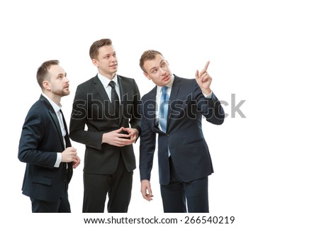 Showing opportunities. Confident businessman pointing away and smiling while standing together with two colleagues. Isolated on white. - stock photo