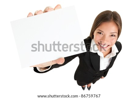 Showing sign - woman holding big business card / paper sign with copy space. Sign and businesswoman face both in focus. High angle full length view of happy smiling woman isolated on white background. - stock photo