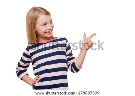 Showing the right direction. Cheerful little girl pointing away and holding hand on hip while standing isolated on white - stock photo