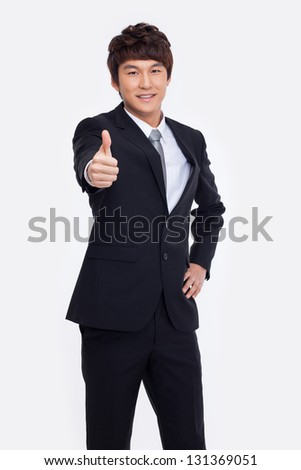 Showing thumb young Asian business man isolated on white background.