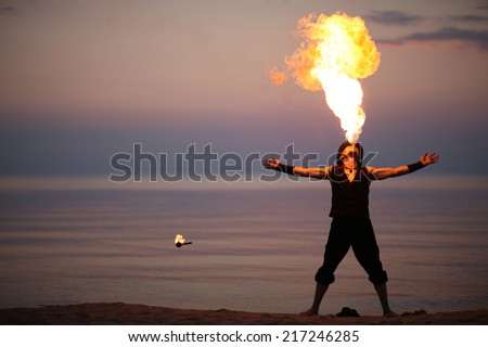 Showman performing amazing fire-breathing - stock photo