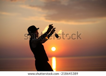 Showman spinning fire poi on sunset background - stock photo
