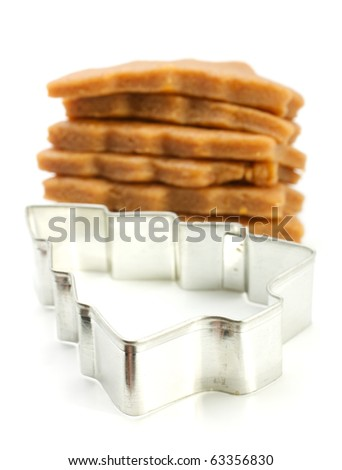 Shows a cookie cutter as a Christmas tree. Behind him lies a pile of ready-made blanks. The background is blurred. Isolated on white background.