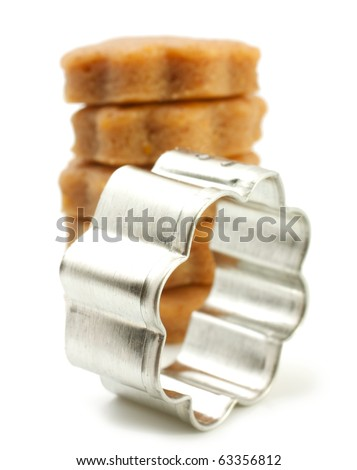 Shows a cookie cutter as a Flowers. Behind him lies a pile of ready-made blanks. The background is blurred. Isolated on white background.