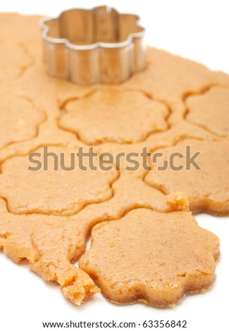 Shows a layer of rolled dough for biscuits. Cut out several shapes for biscuits in the shape of flowers. Isolated on white background. - stock photo