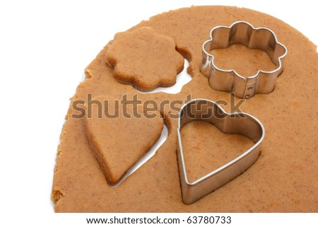 Shows a layer of rolled dough for biscuits. Cut out several shapes for biscuits in the shape of flowers and hearts. Isolated on white background. - stock photo