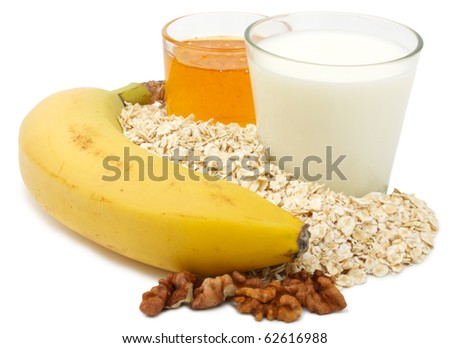 Shows a set of cooking porridge with milk, honey, banana and nuts. Isolated on white background.