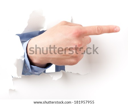 shows the direction of the hand through the torn paper - stock photo