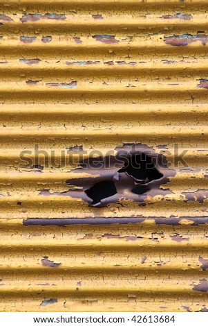 Shrapnel hole in an old metallic panel - stock photo