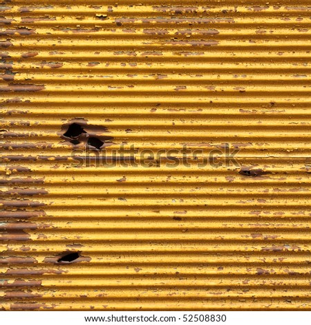 Shrapnel hole in rusty yellow panel - stock photo
