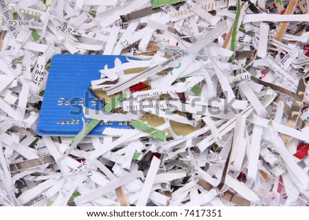 Shredded documents cover an exposed portion of a credit card. - stock photo