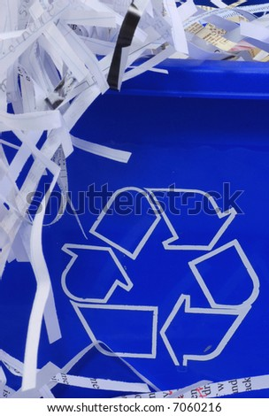 shredded paper spilling out of blue recycle bin - stock photo