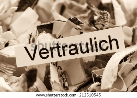 shredded paper tagged confidential, symbol photo for data destruction and confidentiality - stock photo
