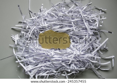 Shredded paper with piece of brown paper in the center  - stock photo