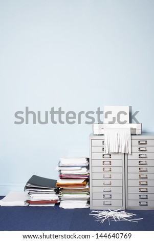 Shredder on file cabinet stack of paperwork on floor in office - stock photo