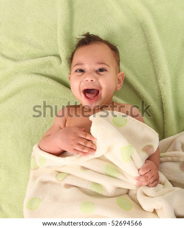 Shrieking Happy Infant Holding a Blanket Lying on His Back - stock photo