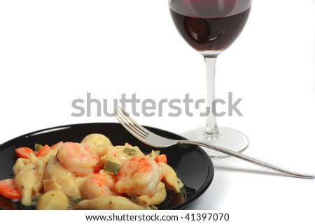 Shrimp Alfredo and red wine isolated over white - stock photo