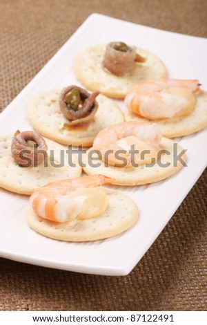 Shrimp and anchovy appetizer served on a white plate. Selective focus, shallow DOF - stock photo