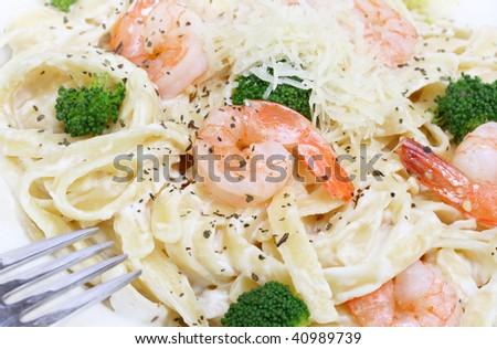 Shrimp and fettuccine Alfredo with broccoli in a macro image. - stock photo
