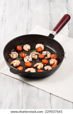 shrimp and mushrooms fried in a pan with tomatoes on wooden background - stock photo