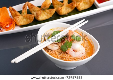 Shrimp and Thai noodle soup bowl with chopsticks along with fried wonton or rangoon type appetizers. - stock photo