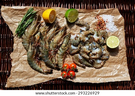 Shrimp are on the light brown parchment paper cut to close the two halves of lime and lemon - stock photo
