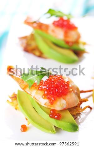 shrimp, avocado and caviar on potato pancakes - stock photo
