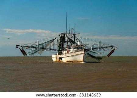 Shrimp boat returning from the sea in harbor - stock photo