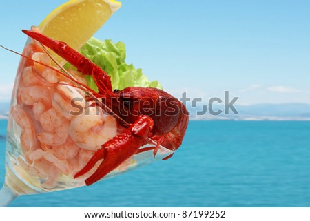 shrimp cocktail with crayfish in the glass isolated on blue sea background - stock photo